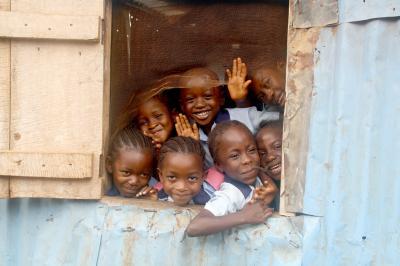 Escolares sonriendo tras una ventana en una escuela de hojalata